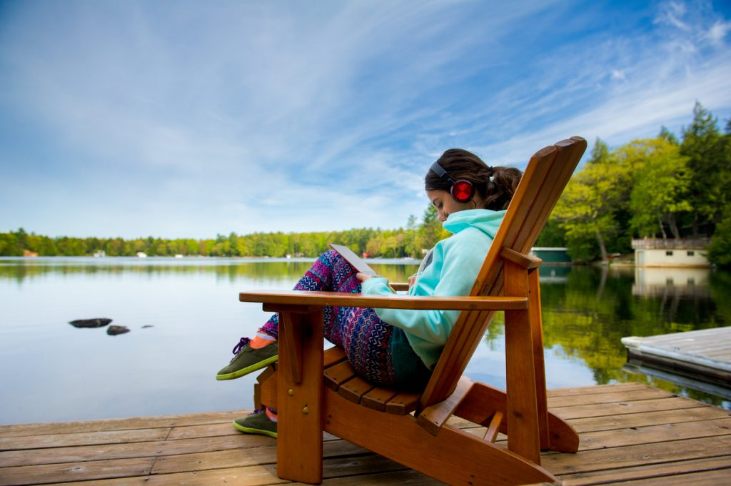girl listening to music near a lake