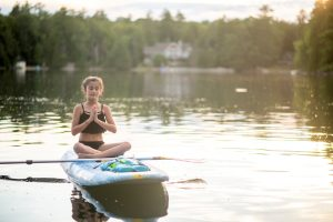 Health benefits of lakefront living: Woman meditating on paddle board