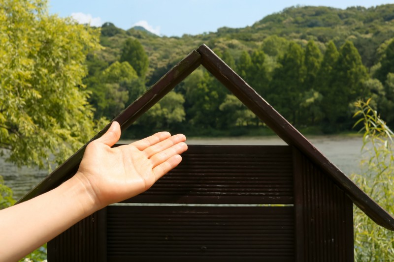 Hand Presenting Wooden House Beside A River
